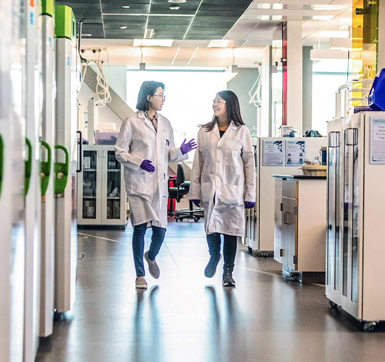 Two lab technicians in white lab coats having a conversation while walking in lab