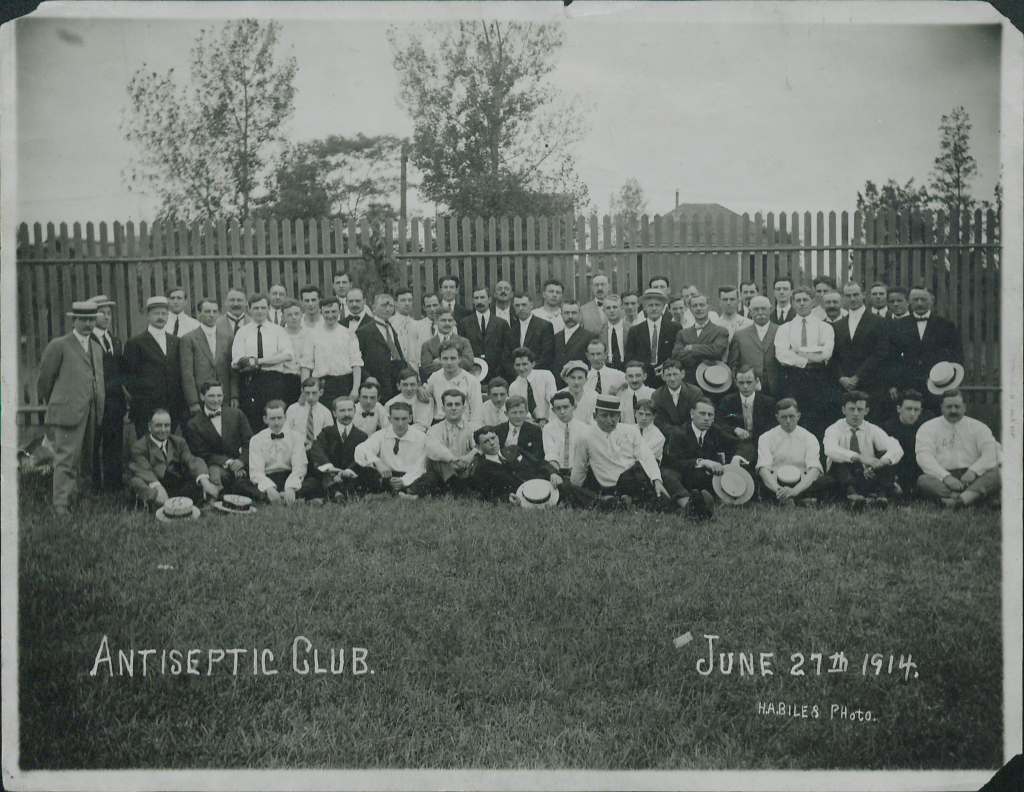 1914 photo of men and women posing in front of fence