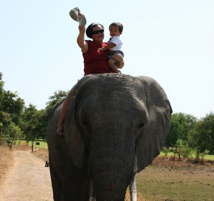 Villar and her son riding an elephant outside of Lusaka, Zambia