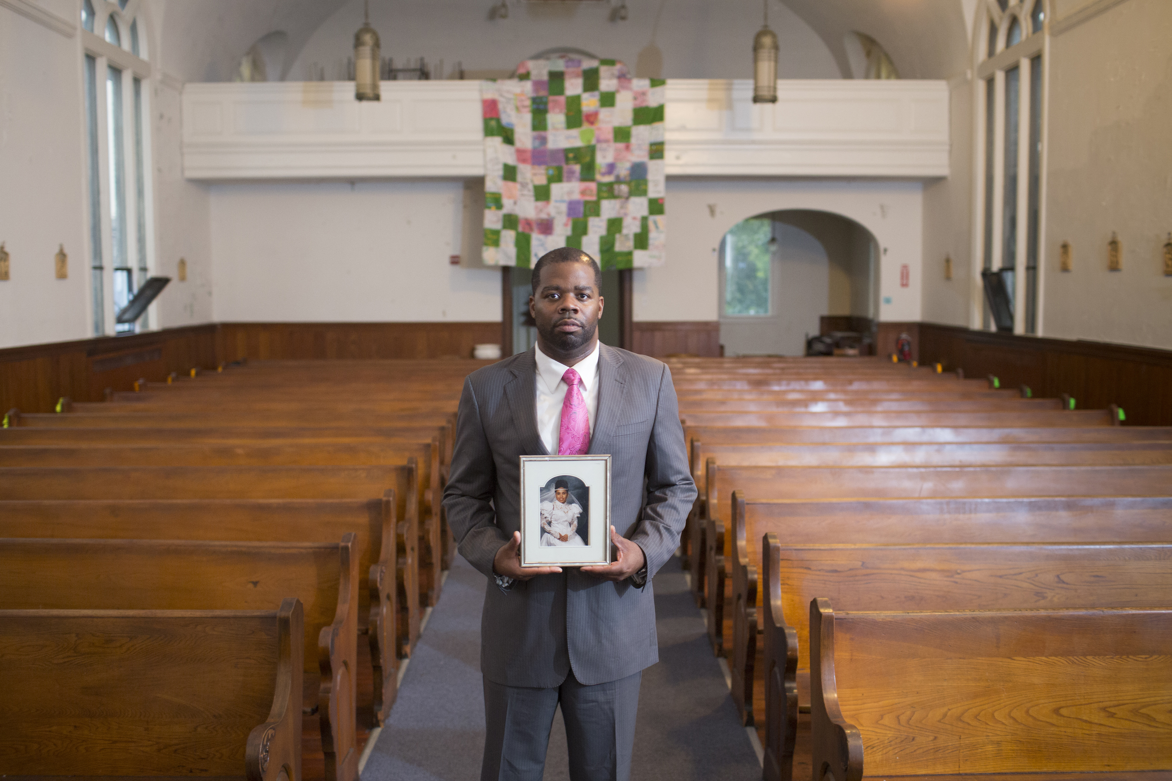 A man holding a picture of a loved one in a church