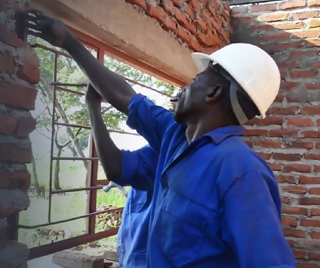 two men working on a brick house
