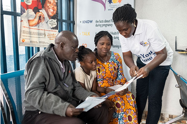 a nurse helping patients fill out paper work