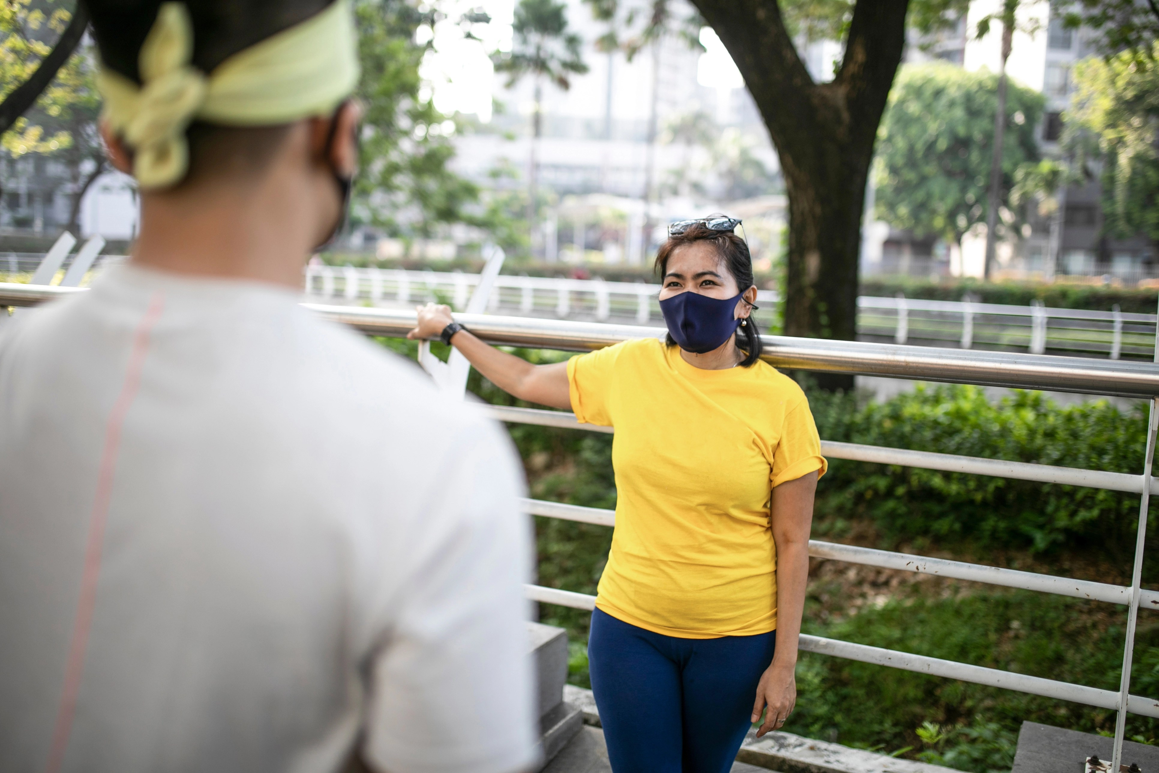 woman wearing a mask leaning against a railing